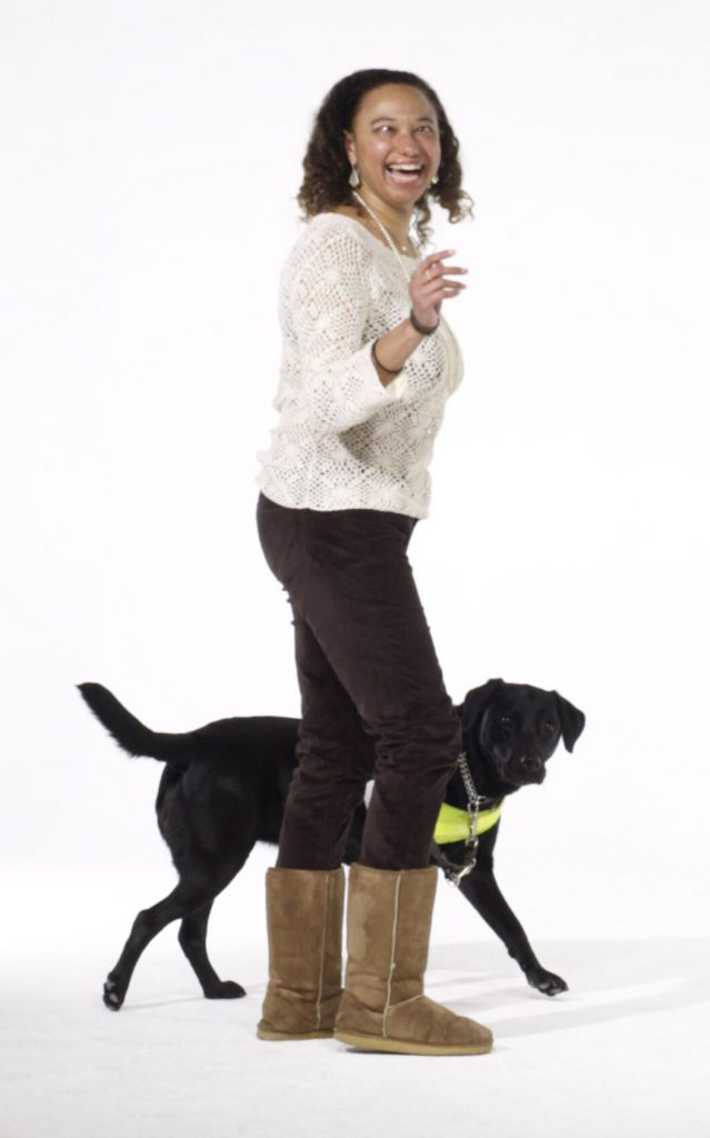 Maria stands and looks at the camera with an animated expression, joined by her black guide dog Penny