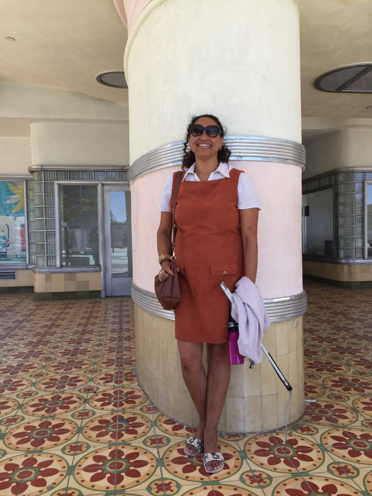 Maria standing in front of a tall column amidst some colourful tiles, on the site of the old Coconut Grove where Lynn first performed