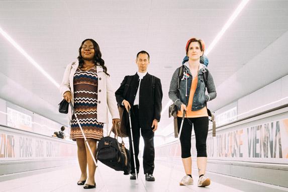 Victoria Oruari, Takashi Kakuchi and Amelia Cavallow walk between travelators at an airport