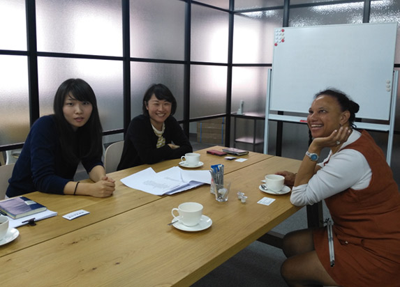 Maria sits at a table in discussion and smiling with Mariko Mori and Mei Harada at The Nippon Foundation.
