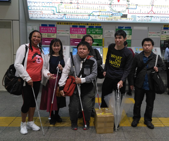 Maria with group of visually impaired tennis players all standing in front of a large Tokyo subway map