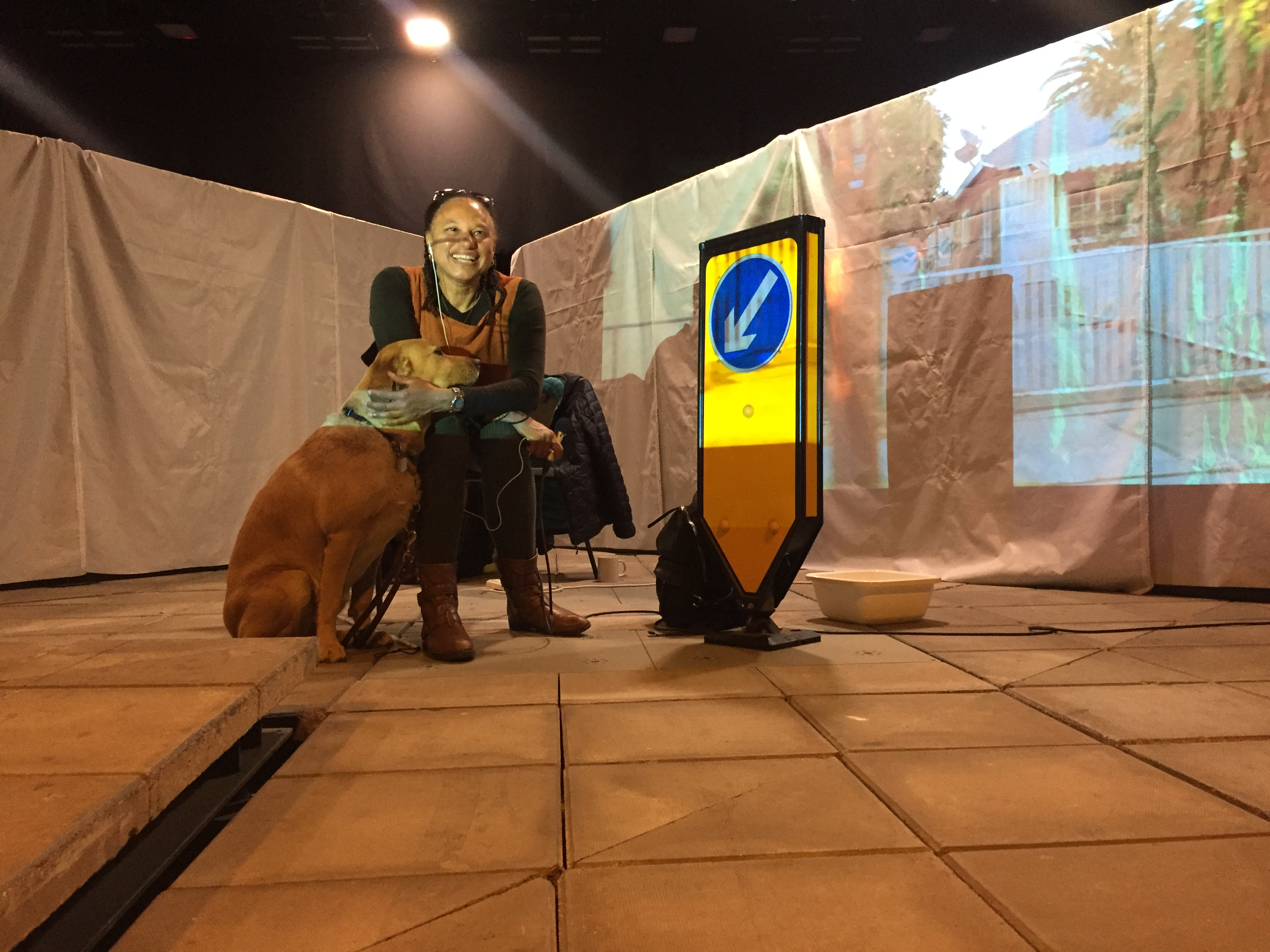 Maria sits between two screens smiling at camera and holding a mic. Her guide dog Bella and a road sign stand nearby