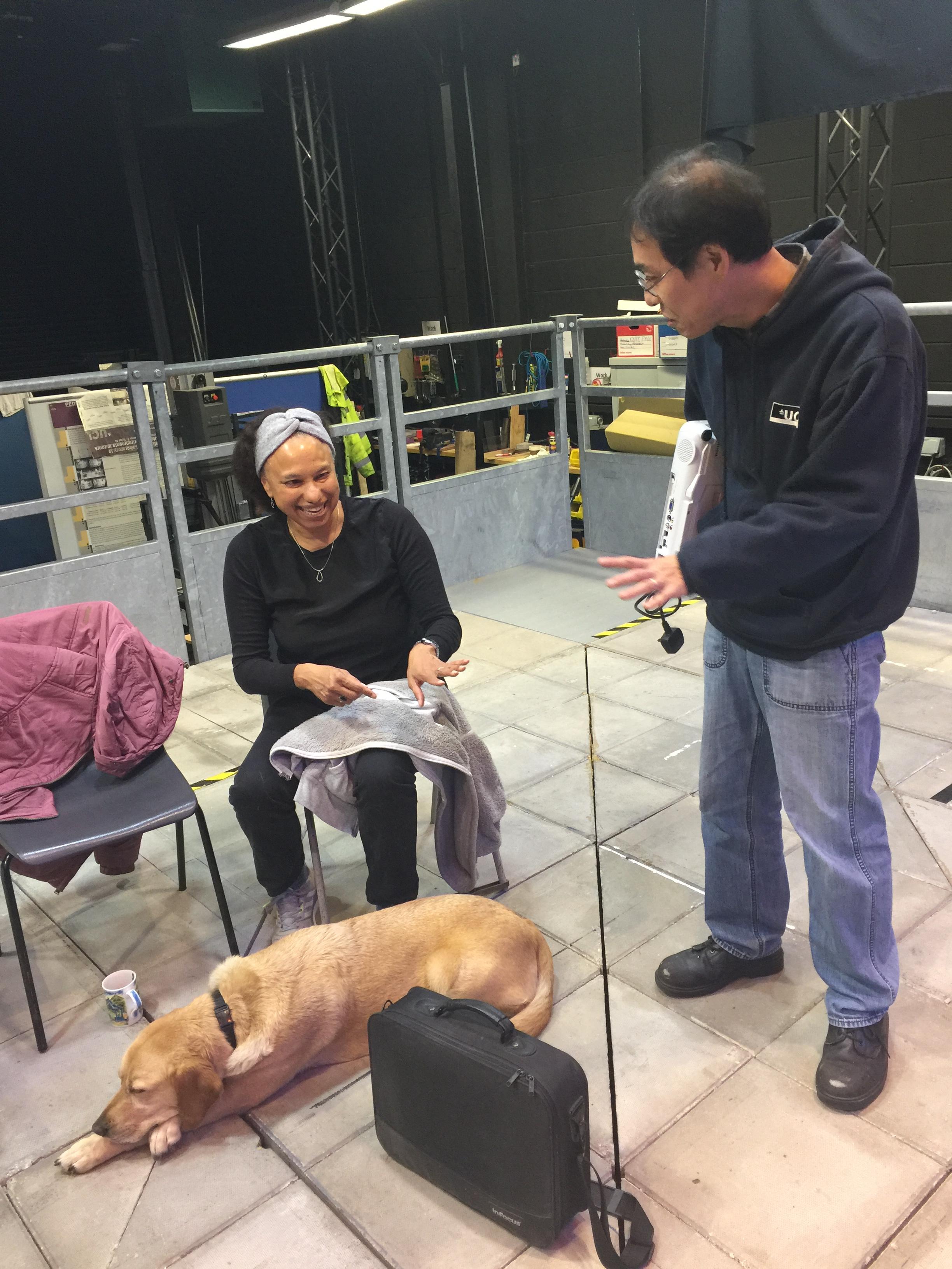 PAMELA technician Tatsuto Suzuki offers a projector to Maria, sitting on platform laughing
