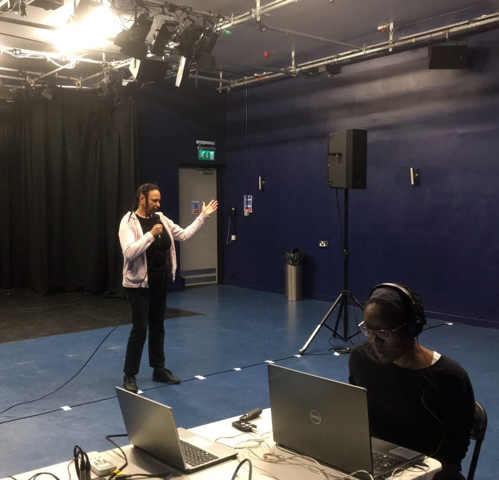 Maria standing in theatre studio  gestures while another woman of colour sits at a laptop