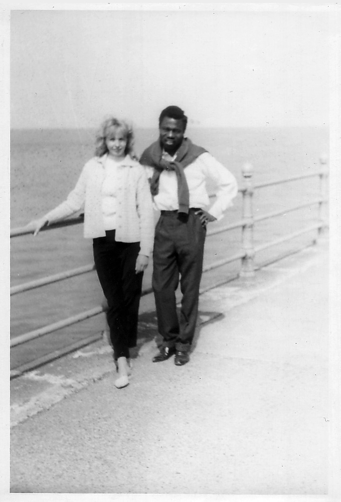 Young black man and white woman standing together by a rail on a seaside promonard smiling out at camera in fashions of the 1960's