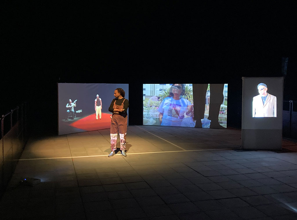 Maria  stands on stage in terracotta dungarees  with a black top underneath  - At the back, large screen left Lynn performs with a guitarist and on screen right there is a blur of shadowy images