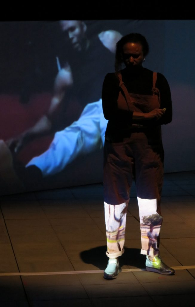 Maria stands thoughtful on stage with Lynn on a long screen  next to her – The light from a projector spreads up Maria's legs like boots