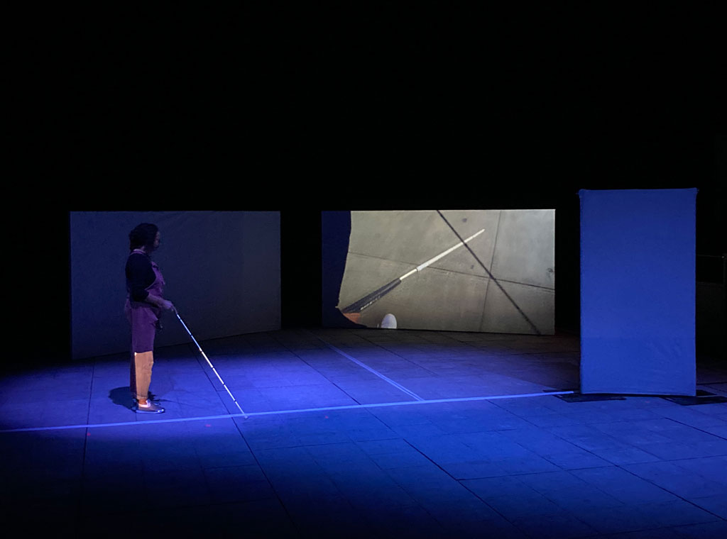 Maria walks  upstage with a white cane while on the large screen to her right shows a white cane  on a side-walk