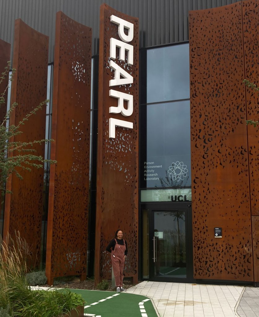 Maria stands  in the doorway under the PEARL sign outside the vast UCL  research facility