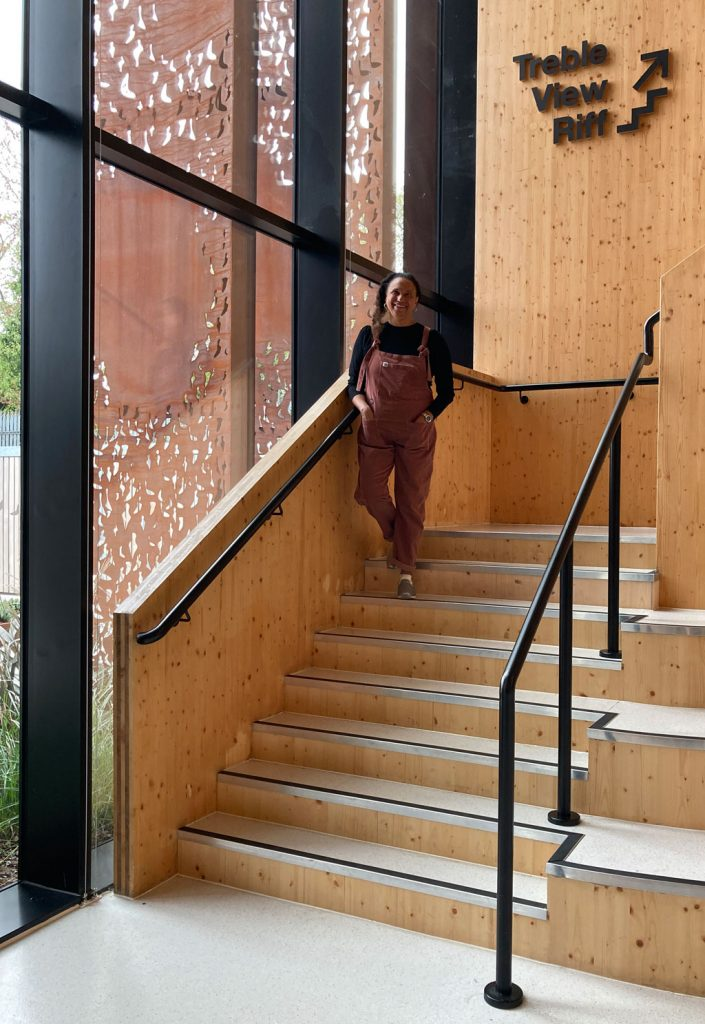 Maria stands on wooden spiral stairs with a glass wall of the Pearl reception area behind